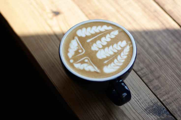 black ceramic tea cup on brown surface